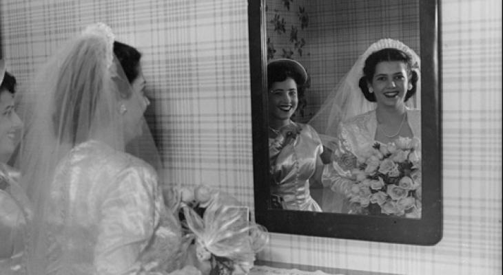 woman in wedding gown looking in mirror