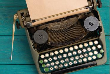 An old-fashioned typewriter with a piece of paper sticking out of it