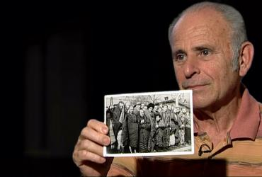 man holding up photo from concentration camp