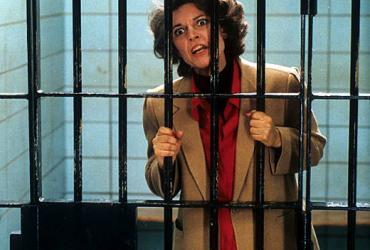 A woman standing in a jail cell holding onto the bars